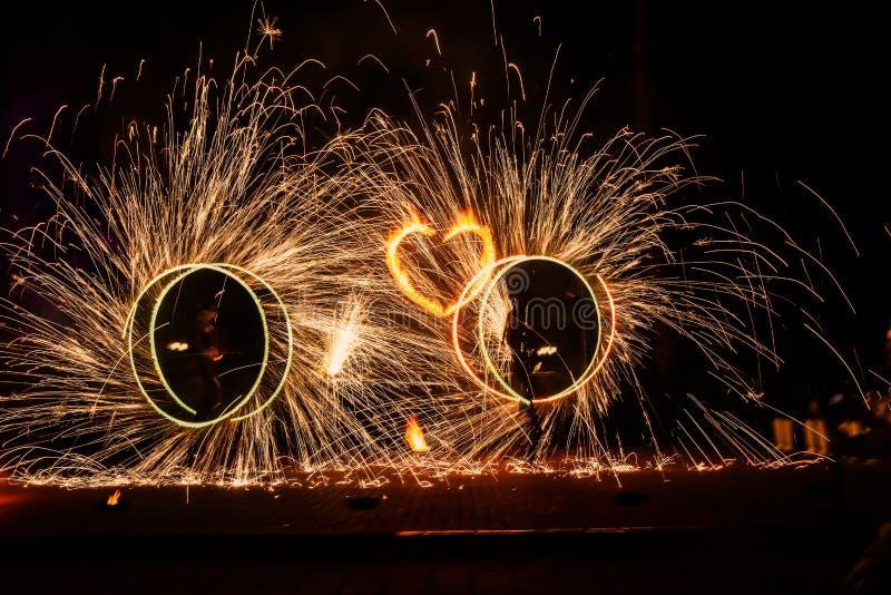 Círculos de la demostración dos del fuego artificial con las chispas y el corazón ardiente imagen de archivo libre de regalías