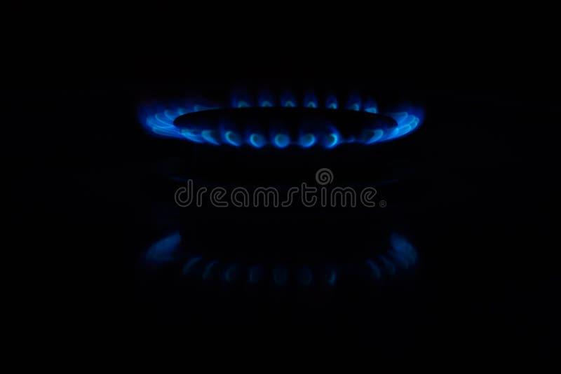 Círculos del fuego en una estufa de gas en la oscuridad Llama azul reflejada en la superficie imágenes de archivo libres de regalías