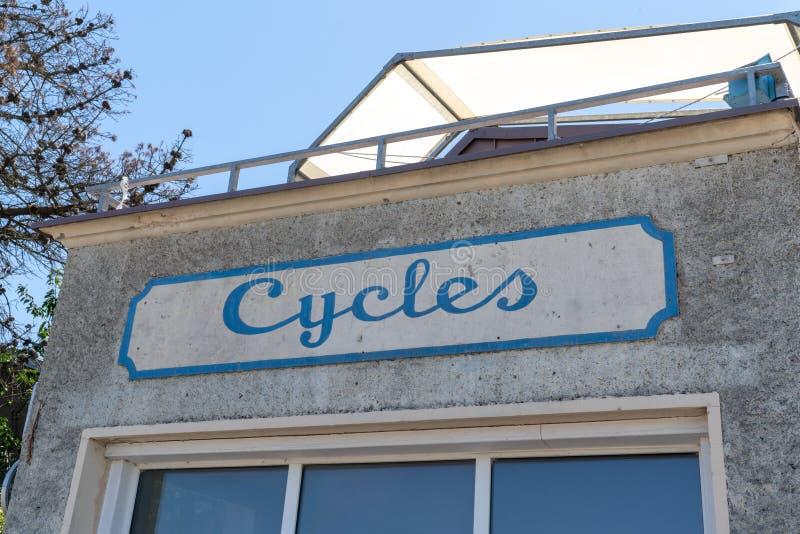 Círculos em francês significa Loja de bicicletas em sinal de enferrujamento antigo em prédio antigo foto de stock