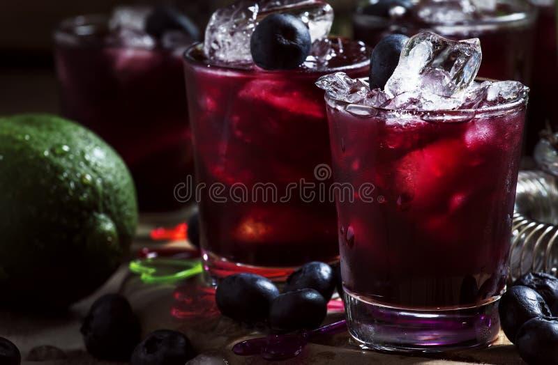 Cóctel alcohólico con el licor, arándano, zumo de lima, hielo machacado, herramientas de la barra en el fondo negro, foco selecti imagen de archivo