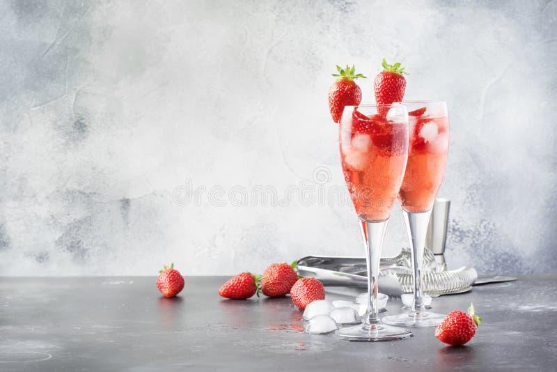 Cóctel alcohólico de Rossini con el vino espumoso, el puré y el hielo italianos en vidrios del champán, lugar de la fresa para el foto de archivo libre de regalías