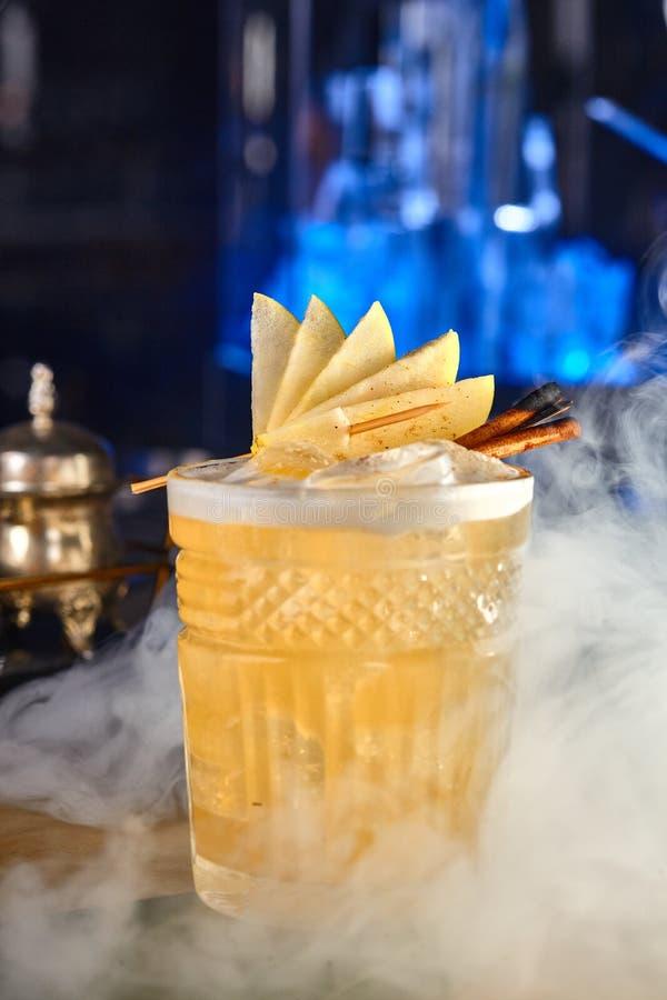 Cóctel alcohólico largo de manzanas y del canela en humo fotografía de archivo