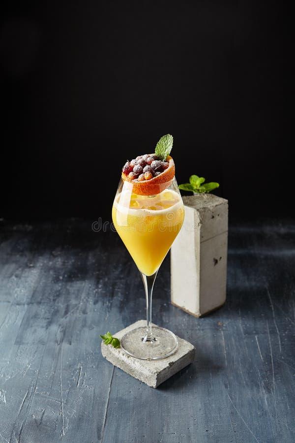 Cóctel amarillo del paraíso con la ginebra, el melocotón, la menta y las bayas rojas C imagen de archivo