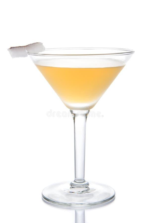 Cóctel amarillo del plátano en el vidrio de martini con el limón y el coco s fotografía de archivo libre de regalías