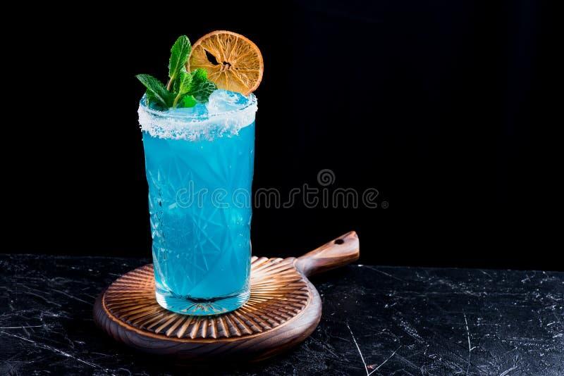 Cóctel azul con el hielo, adornado con la menta y la rebanada de naranja seca en glassm tallado hermoso en fondo negro imágenes de archivo libres de regalías