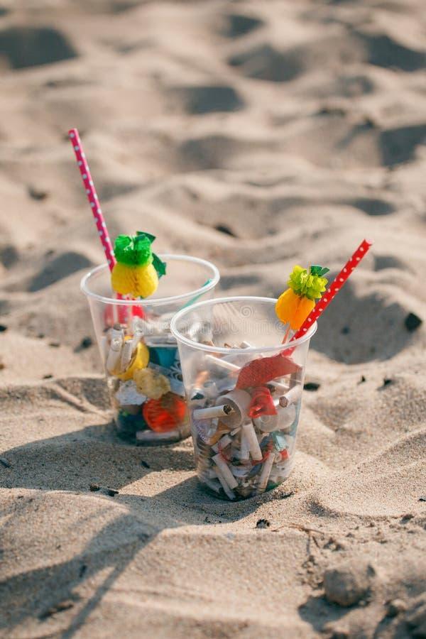 Cóctel con basura y la decoración tropical en la playa limpia Contaminación plástica del océano, crisis ambiental No diga ningún  imagen de archivo libre de regalías