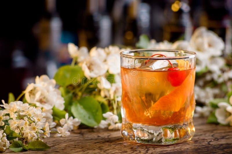 Cóctel con el whisky y la cáscara de naranja en un contador de la barra en un fondo floral fotografía de archivo libre de regalías