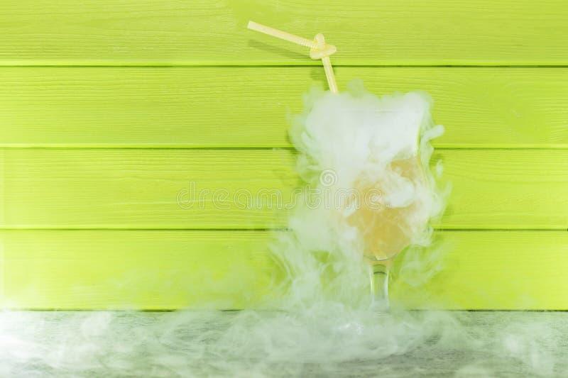 Cóctel con nitrógeno líquido Cóctel de enfriamiento del verano en un vidrio de cristal con una paja Nitr?geno l?quido foto de archivo libre de regalías