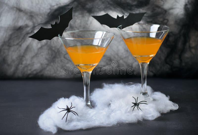 Cóctel de la calabaza de Halloween, bebida anaranjada tóxica adornada con las arañas, telaraña y palos negros en fondo oscuro fotos de archivo libres de regalías