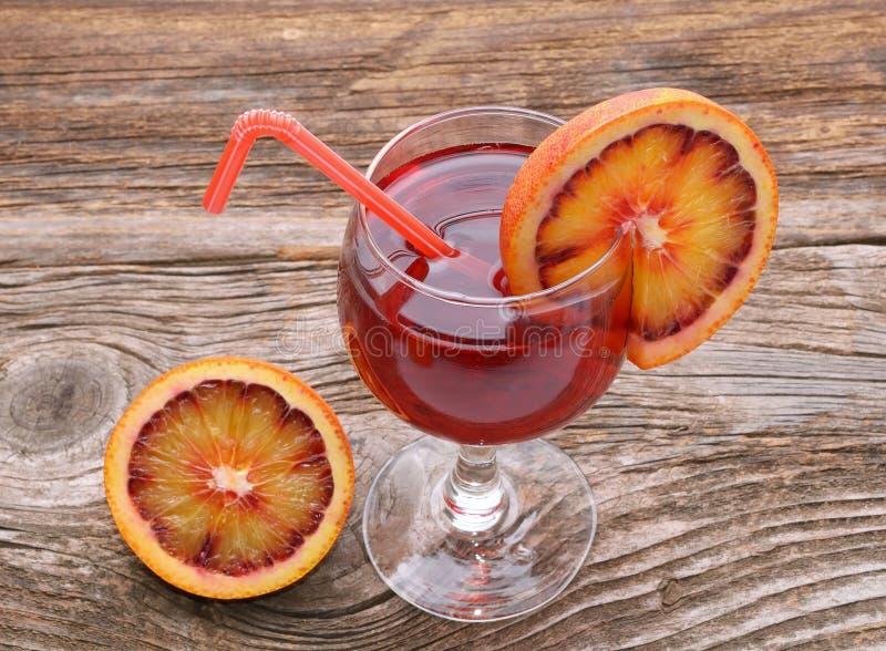 Cóctel de la naranja de sangre con las rebanadas de naranja de sangre en la tabla de madera imagen de archivo libre de regalías