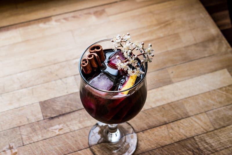 Cóctel de la sangría en copa de vino con el limón, el canela, las frutas y el hielo fotografía de archivo