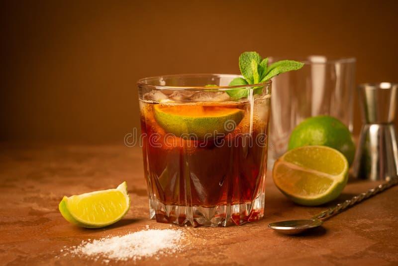 Cóctel de los cubos y de la cal de hielo del ron y de la cola en un cubilete de cristal en un fondo marrón oscuro Bebida alcohóli imagenes de archivo