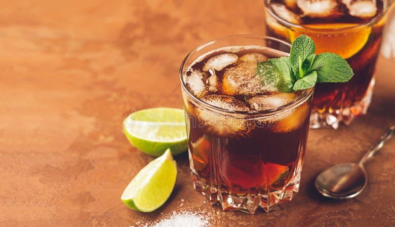 Cóctel de los cubos y de la cal de hielo del ron y de la cola en un cubilete de cristal en un fondo marrón oscuro Bebida alcohóli foto de archivo libre de regalías
