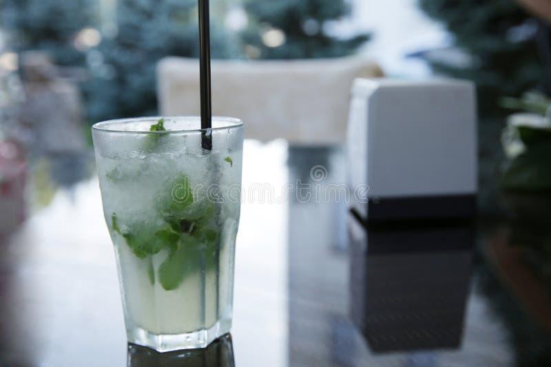 Cóctel de Mojito hecho de la cal, de la menta y del hielo en un vidrio con una paja en una tabla de cristal con la reflexión fotografía de archivo