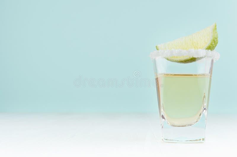 Cóctel del alcohol para la celebración - tequila de oro con el borde de la sal y cal verde jugosa en la barra de color de la ment fotografía de archivo