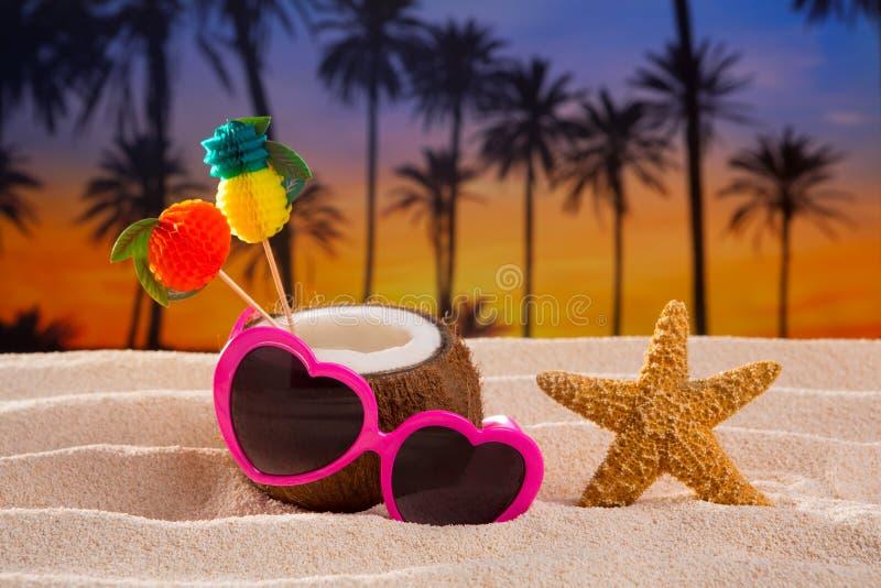 Cóctel del coco en las gafas de sol tropicales del corazón de la playa de la arena fotos de archivo libres de regalías