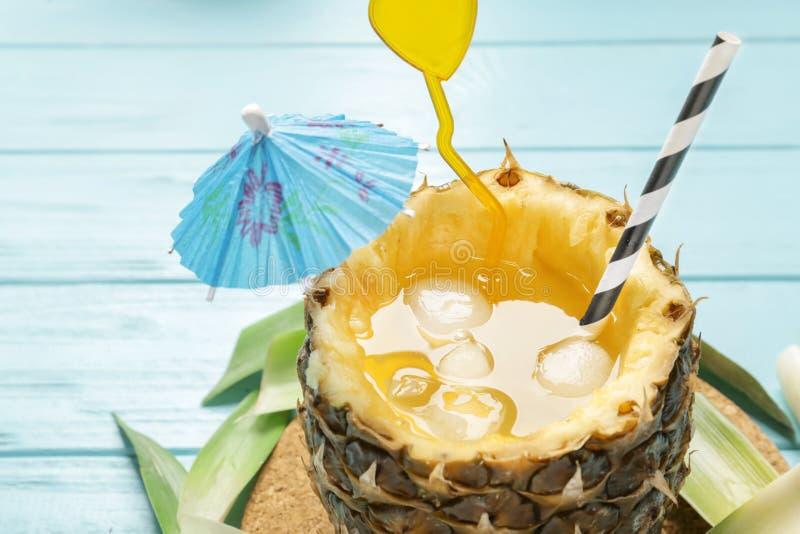 Cóctel delicioso frío en piña en fondo de madera ligero imagen de archivo libre de regalías