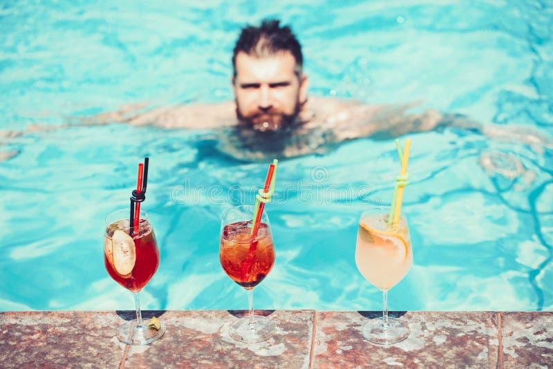 Cóctel feliz de la bebida del hombre en la piscina Vacaciones de verano id?licas fotografía de archivo libre de regalías