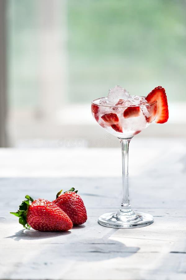 Cóctel frío con la vodka, el jarabe de fresa, las fresas frescas y el hielo machacado en vidrios en un fondo ligero foto de archivo libre de regalías