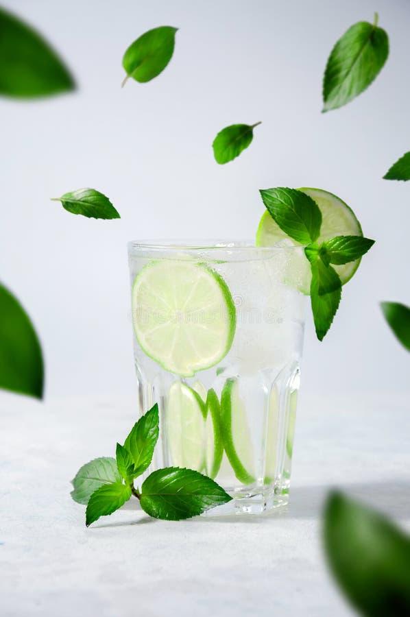 Cóctel Mojito o limonada con la cal, la menta y el hielo en fondo ligero Bebidas frescas del verano del concepto fotografía de archivo