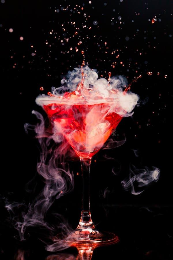 Cóctel rojo con el vapor del chapoteo y del hielo fotografía de archivo