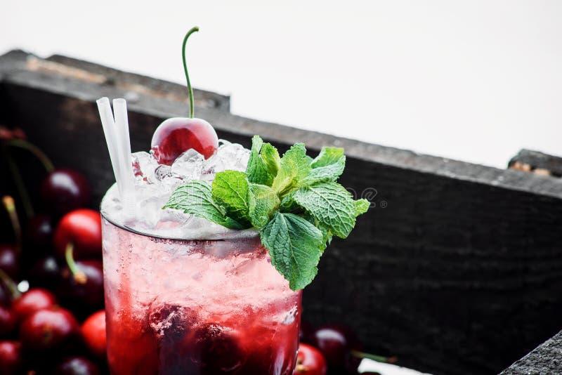 Cóctel rojo con hielo, la menta y la cereza en un fondo de la baya fotografía de archivo libre de regalías