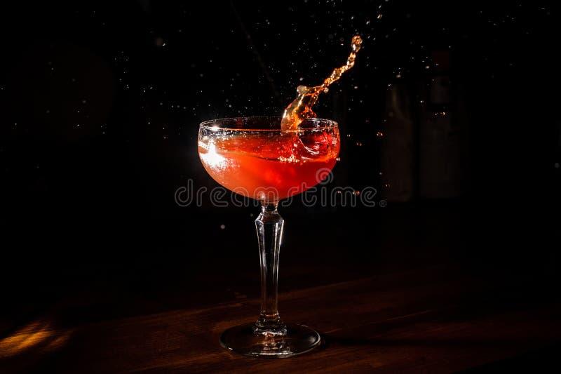 Cóctel rojo de martini que salpica en el vidrio en fondo negro fotografía de archivo libre de regalías