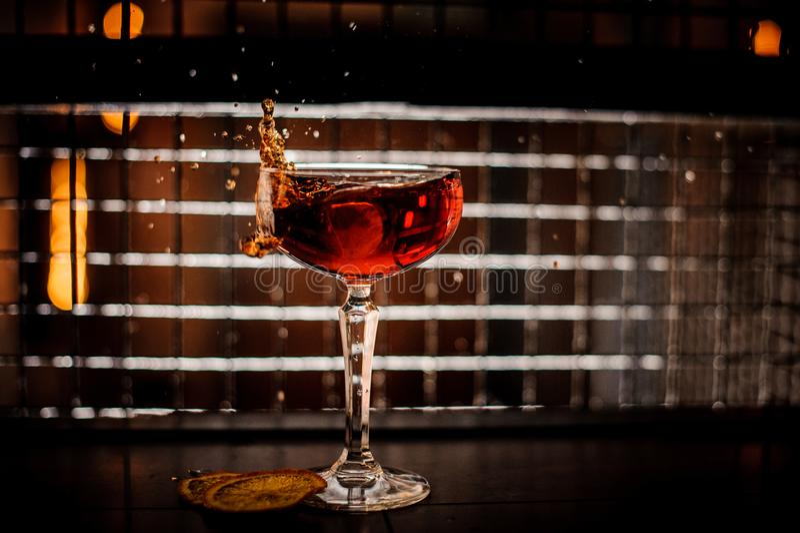 Cóctel rojo de martini que salpica en el vidrio en fondo oscuro foto de archivo libre de regalías