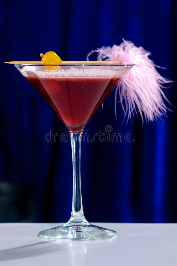 Cóctel rosado alcohólico en un vidrio de martini con la paja, d baja foto de archivo