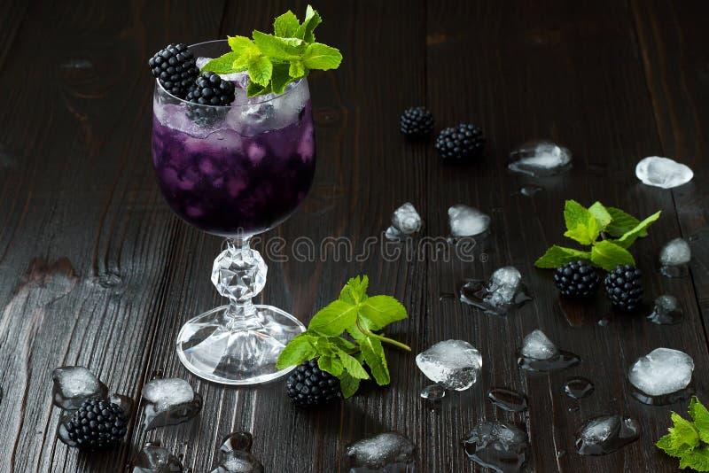 Cóctel sabroso de la zarzamora en copa de vino con la menta y el hielo en la tabla de madera oscura Limonada de la baya del veran fotografía de archivo