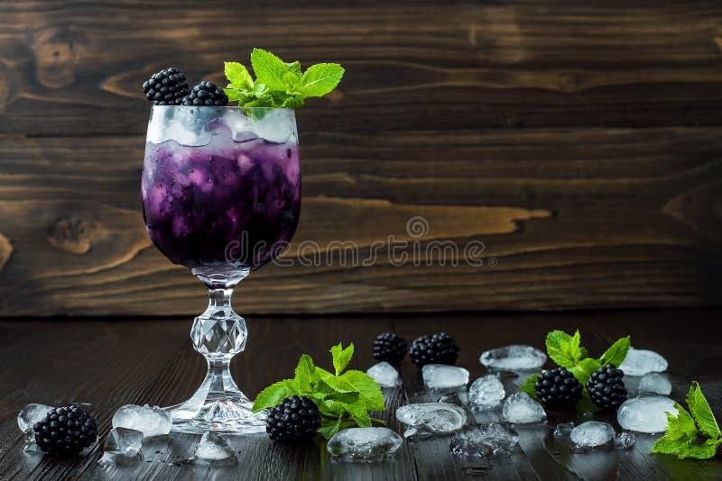 Cóctel sabroso de la zarzamora en copa de vino con la menta y el hielo en la tabla de madera oscura Limonada de la baya del veran fotos de archivo