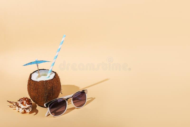 Cóctel tropical en coco con la paja, un paraguas, gafas de sol, cáscara en fondo amarillo El concepto de relajación, verano fotos de archivo