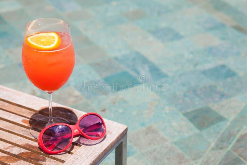 Cóctel y gafas de sol exóticos por la piscina de un hotel de lujo imagenes de archivo