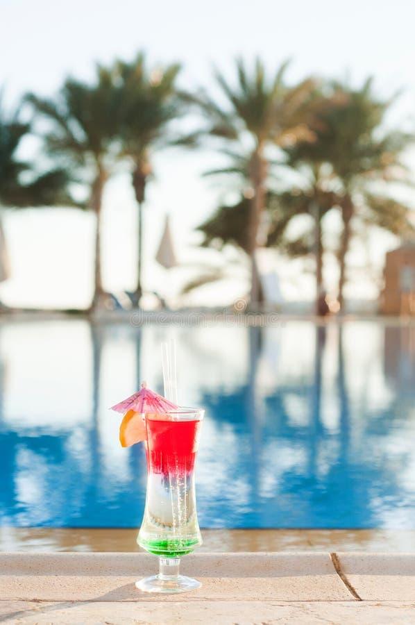 Cócteles coloreados en un fondo del agua Cócteles coloridos cerca de la piscina partido de la playa Bebidas del verano Bebidas ex imagen de archivo libre de regalías