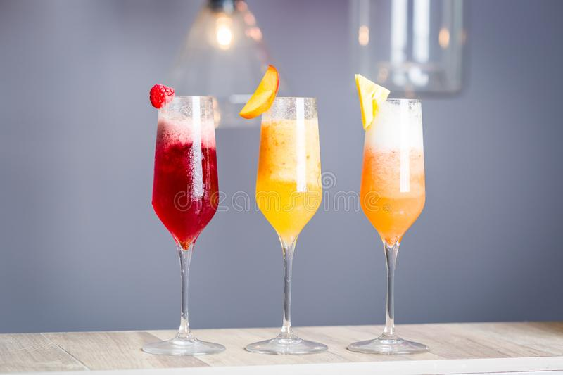 Cócteles coloridos del verano con Prosecco, la clase tres de ensaladas de fruta - frambuesa, melocotón y piña, papel pintado hori fotografía de archivo