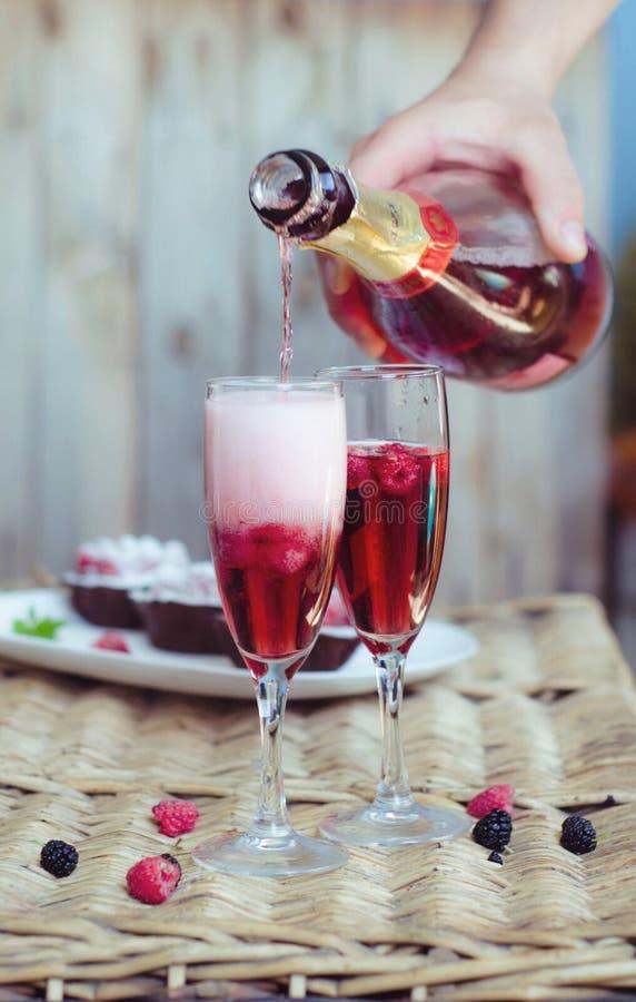 Cócteles de Champán con las frambuesas por una tarde romántica en una tabla de madera Color líquido rosado, vidrios con las burbu foto de archivo