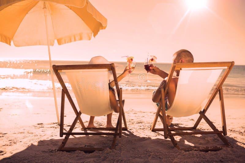 Cócteles de consumición de los pares felices mientras que se relaja en sus sillas de cubierta libre illustration