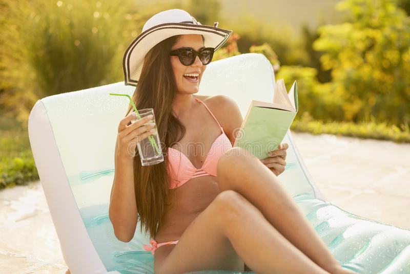 Cócteles de consumición de la mujer y lectura de un libro por la piscina fotografía de archivo libre de regalías