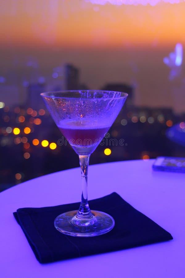 Cócteles en el balcón de Skycraper con puesta del sol imagenes de archivo