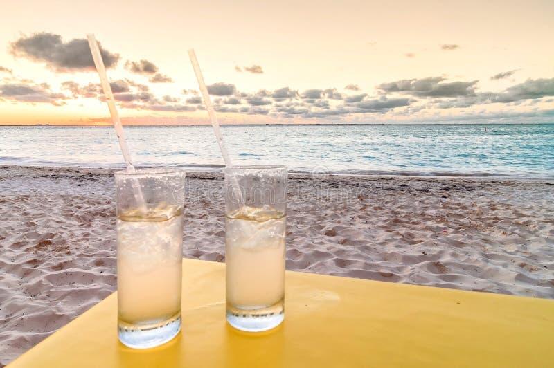 Cócteles en la playa tropical en la puesta del sol fotografía de archivo