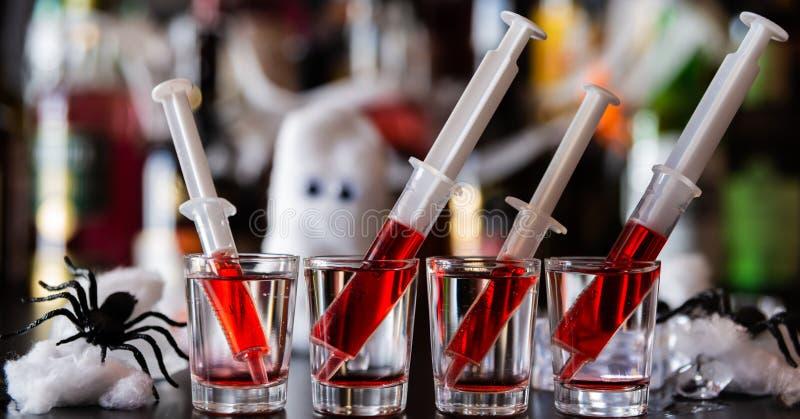 Cócteles espeluznantes del partido de Halloween con las jeringuillas de syru de la granadina fotografía de archivo libre de regalías