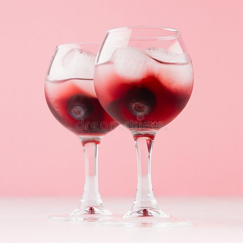 Cócteles fríos tradicionales árticos rojos jugosos con los cubos de hielo, arándano en copas mojadas en el fondo rosado en co fotos de archivo