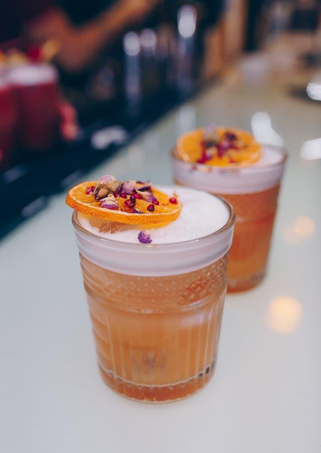 Cócteles jugosos del arte de la pierna de cristal famosa dulce con la bebida inspirada autor decorativo del cóctel en contador de imagen de archivo