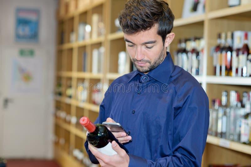 Código de barras da exploração do Sommelier na garrafa de vinho através do smartphone imagem de stock royalty free