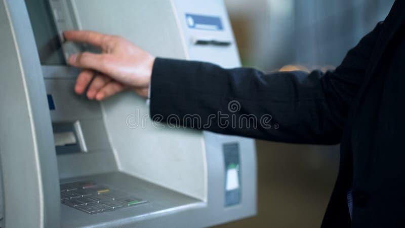 Código del perno del cliente que entra en el cajero automático para recibir el dinero, servicios bancarios, retirándose fotografía de archivo libre de regalías