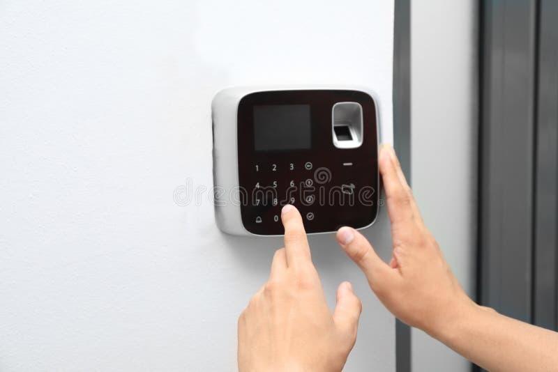 Código entrando do homem novo no teclado do sistema de alarme fotografia de stock