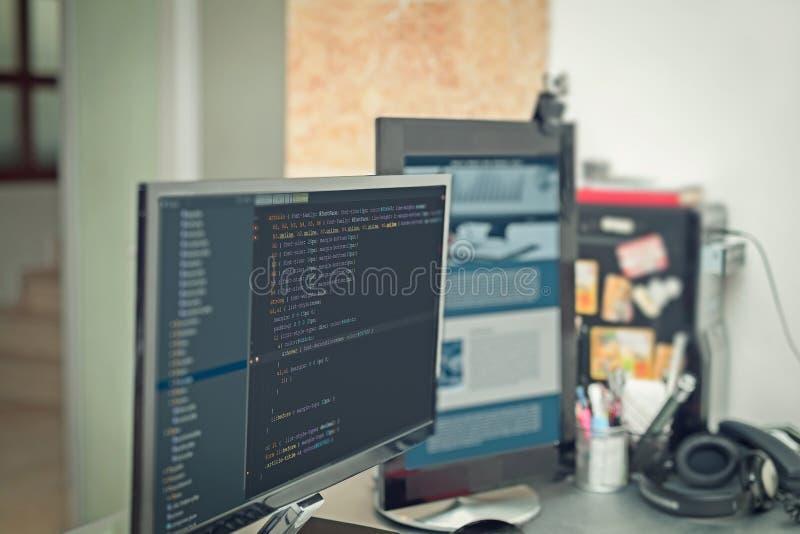 Códigos del sitio web en oficina de AR del monitor de computadora fotografía de archivo