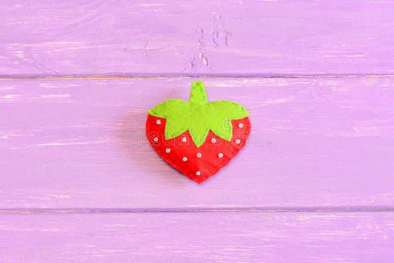 Cómo dar cosa a los niños fresa del juguete step preceptoral Los niños sentían la fresa del juguete en fondo de madera púrpura imagen de archivo libre de regalías