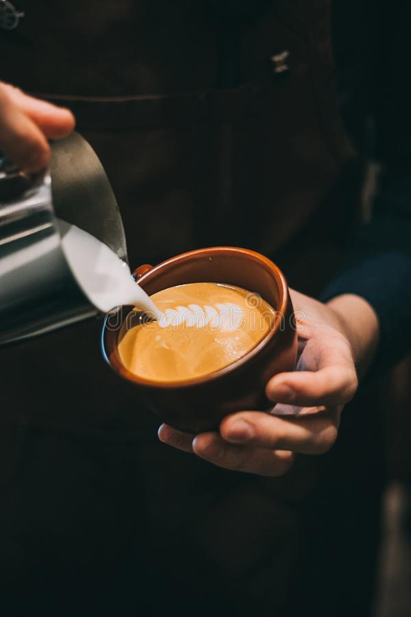 Cómo hacer arte del latte por el foco del barista en leche y café fotos de archivo libres de regalías