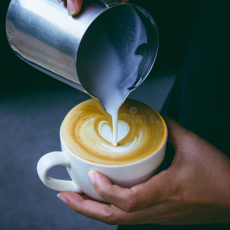 Cómo hacer el café del arte del latte de la hembra de Barista fotos de archivo libres de regalías